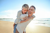 istock Mature couple playing on the beach at sunset or sunrise. 962382656