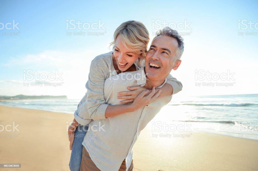 Älteres Paar spielen am Strand bei Sonnenauf- oder Sonnenuntergang. – Foto