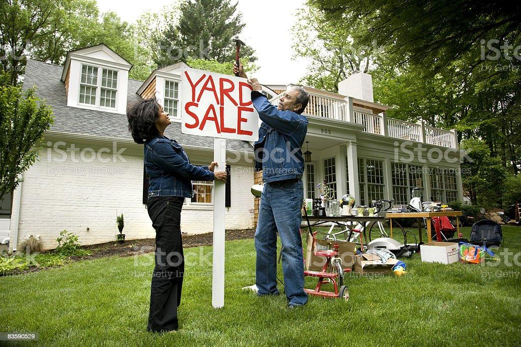 Coppia matura mettere un cartello di vendita per iarda foto stock royalty-free