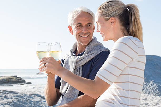 mature couple raising toast - mid volwassen koppel stockfoto's en -beelden