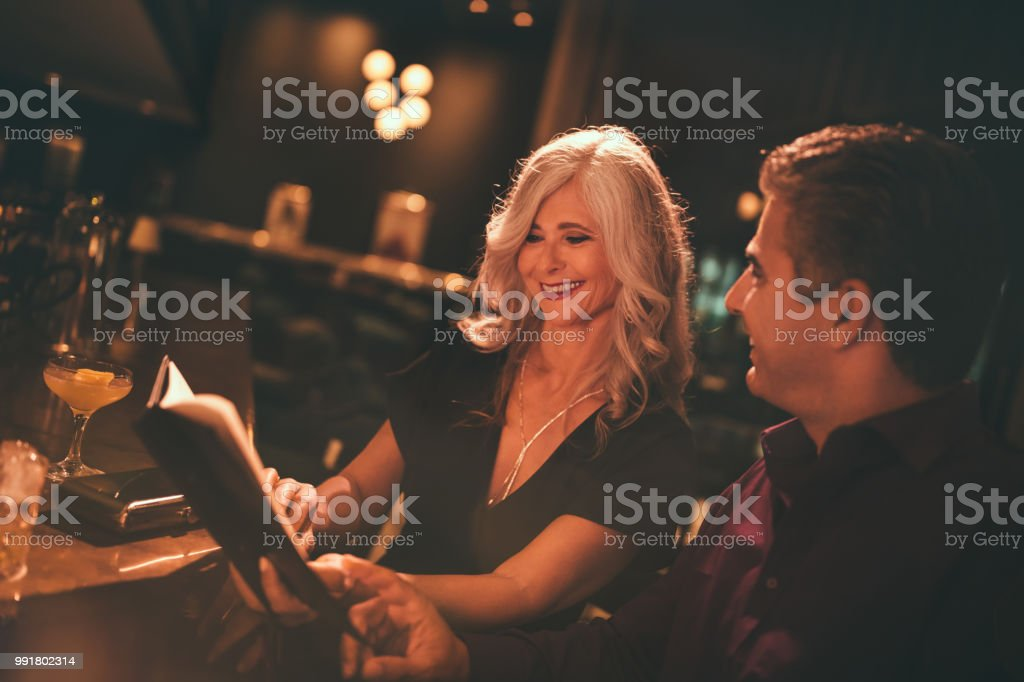 Smiling senior couple reading the menu at luxurious bar and...