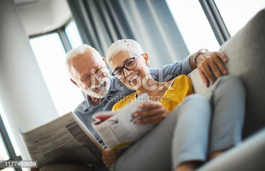 Closeup low angle view of a mid 60's couple sitting on a couch and reading magazines. They are talking and sharing some laughs.