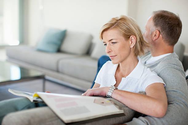 mature couple reading on sofa - woman home magazine stockfoto's en -beelden