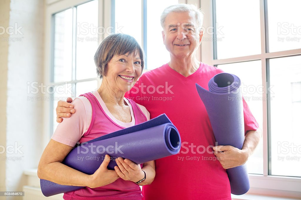 Mature couple ready for yoga workout stock photo