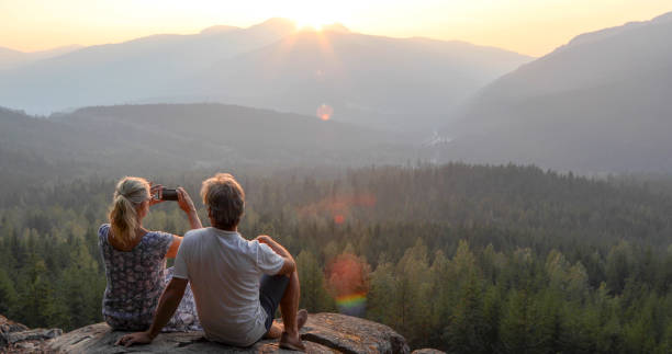 Mature couple relax on mountain ledge, look out to view She takes smart phone pic.The sun is rising ahead of them over the mountains sun shining through dresses stock pictures, royalty-free photos & images