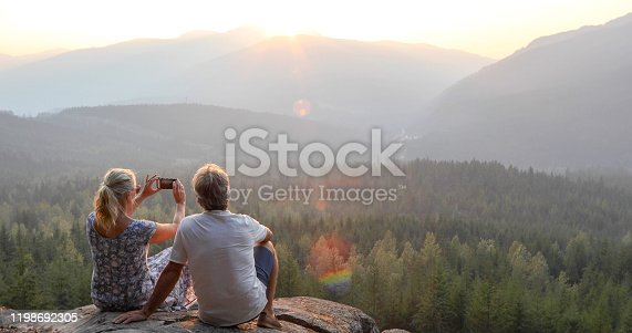istock Mature couple relax on mountain ledge, look out to view 1198692305