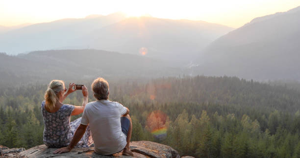 Mature couple relax on mountain ledge, look out to view She takes smart phone pic.The sun is rising ahead of them over the mountains canadian rockies stock pictures, royalty-free photos & images