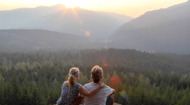 Mature couple relax on mountain ledge, look out to view The sun is rising ahead of them over the mountains sun shining through dresses stock pictures, royalty-free photos & images