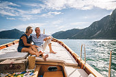 istock Mature couple relax on sailboat moving through Lake Lugano 1291612564