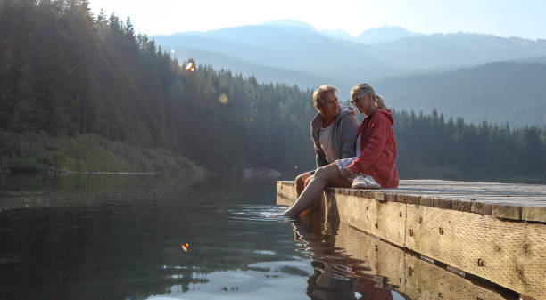Mature couple relax on wooden pier, looks out across lake stock photo