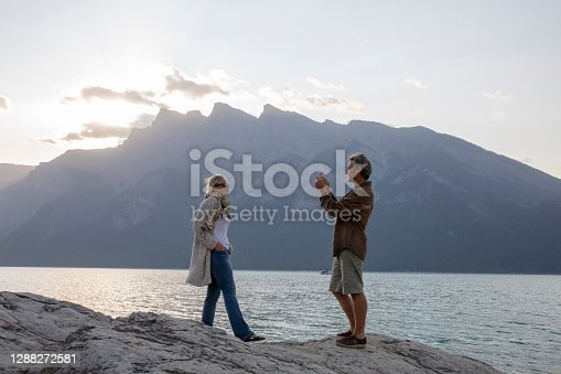 They look off to distant scene and take photos of Canadian Rockies in the distance with smart phone