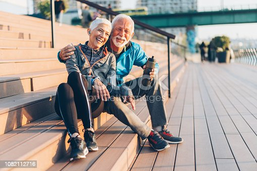 Mature smiling couple relaxing after work out outdoor