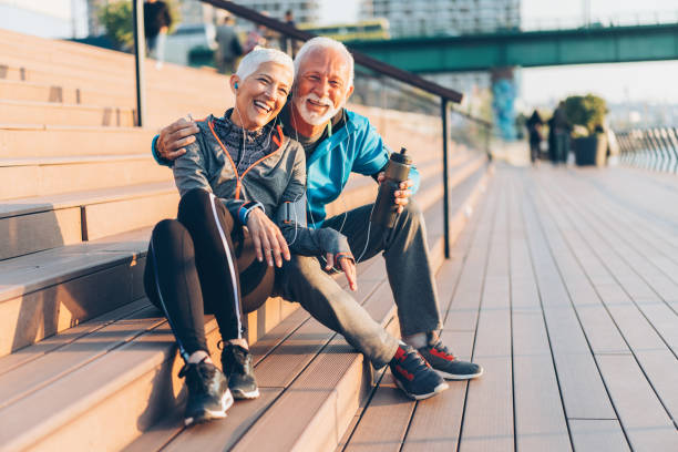 Mature couple relaxing after work out Mature smiling couple relaxing after work out outdoor mature couple stock pictures, royalty-free photos & images