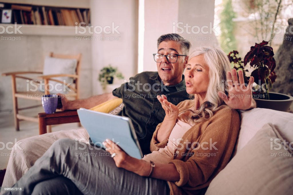 Mature Couple Relaxing At Home And Making Videocall On Tablet Stock