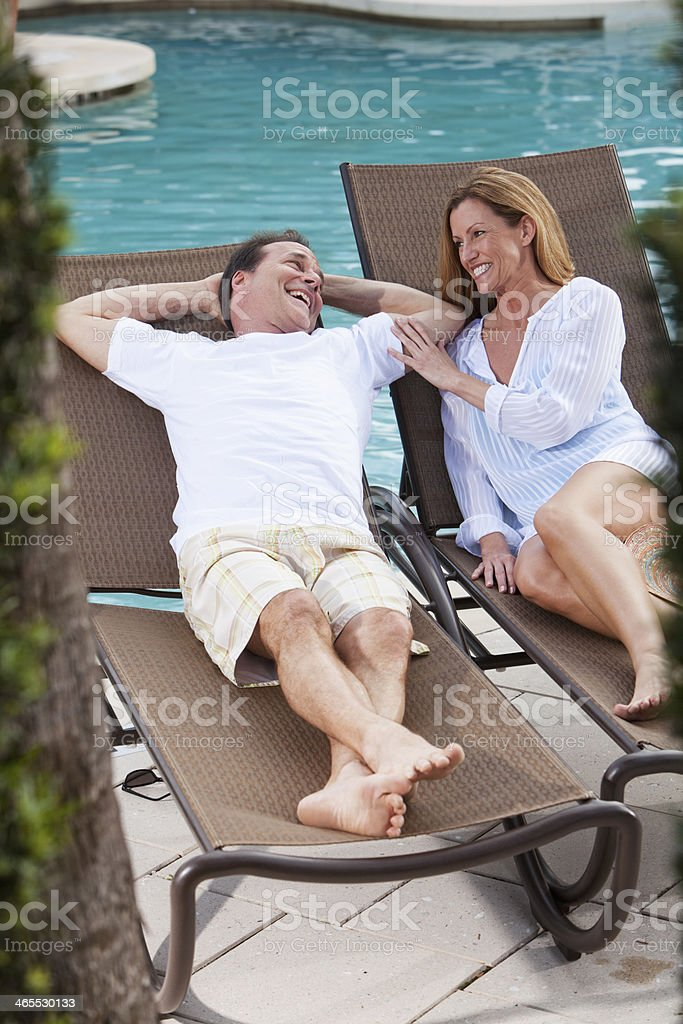 Mature couple relaxing by pool stock photo