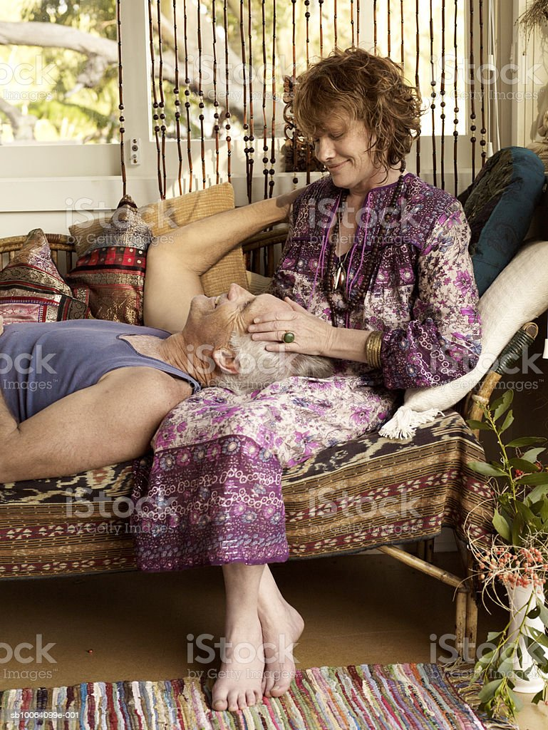 Mature couple relaxing by window royalty-free stock photo