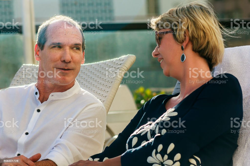 Mature couple relaxing in outdoor chairs stock photo