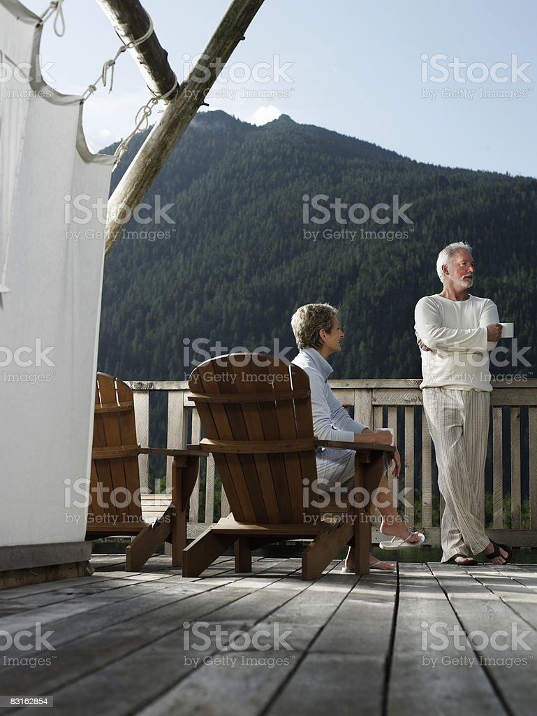 Mature couple relaxing on deck outside tent. royalty free stockfoto
