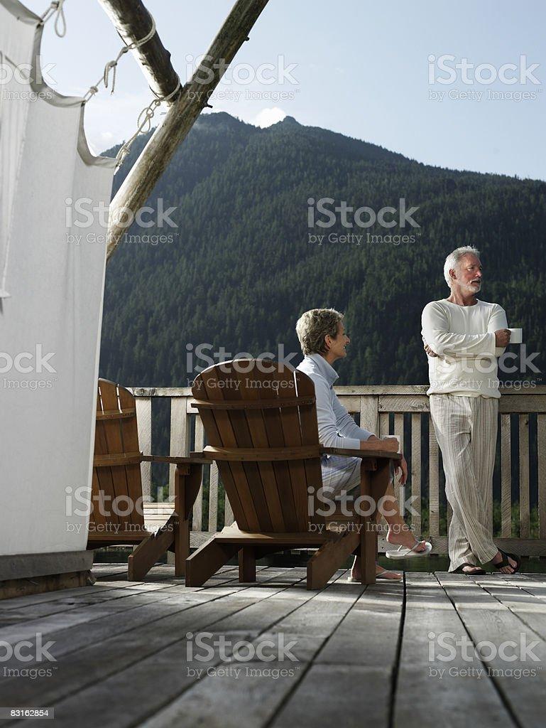 Mature couple relaxing on deck outside tent. royaltyfri bildbanksbilder