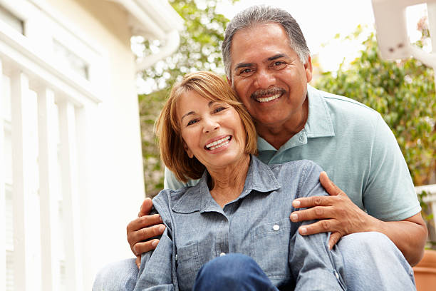 Mature couple relaxing outdoors A close-up of a smiling senior couple.  The man and woman are wearing light blue shirts and are seated.  The woman is in front of the man, and the man's hands are embracing her shoulders.  Out-of-focus bushes are visible in the background. latin american and hispanic ethnicity stock pictures, royalty-free photos & images