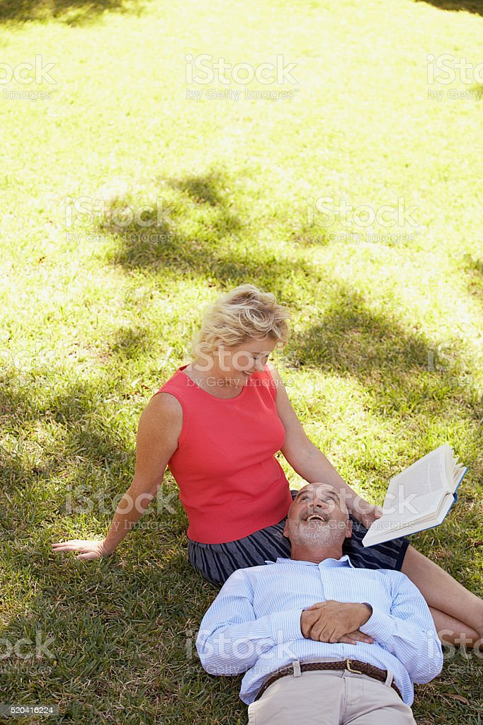 Mature couple relaxing with a book stock photo