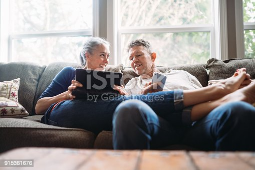 istock Mature Couple Relaxing with Tablet and Smartphone 915361676