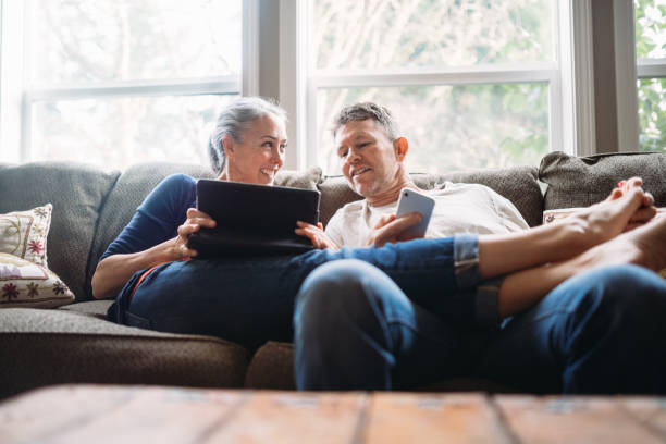 mature couple relaxing with tablet and smartphone - tablet stock photos and pictures