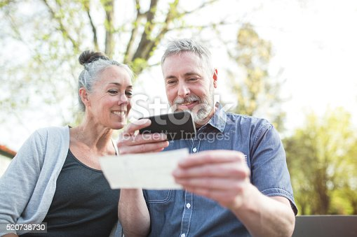A gray haired but youthful looking couple in their 50's enjoy time with each other in a beautiful outdoor setting, the sun casting a golden glow on the scene.   The man takes a picture of a check with his smart phone for a Remote Deposit Capture to his bank.