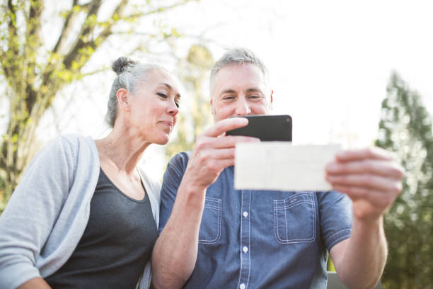 mature couple remote banking with phone - deposit slip stock photos and pictures