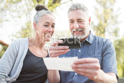 A gray haired and youthful looking couple in their 50's enjoy time with each other in a beautiful outdoor setting, the sun casting a golden glow on the scene. The man takes a picture of a check with his smart phone for a Remote Deposit Capture to his bank.