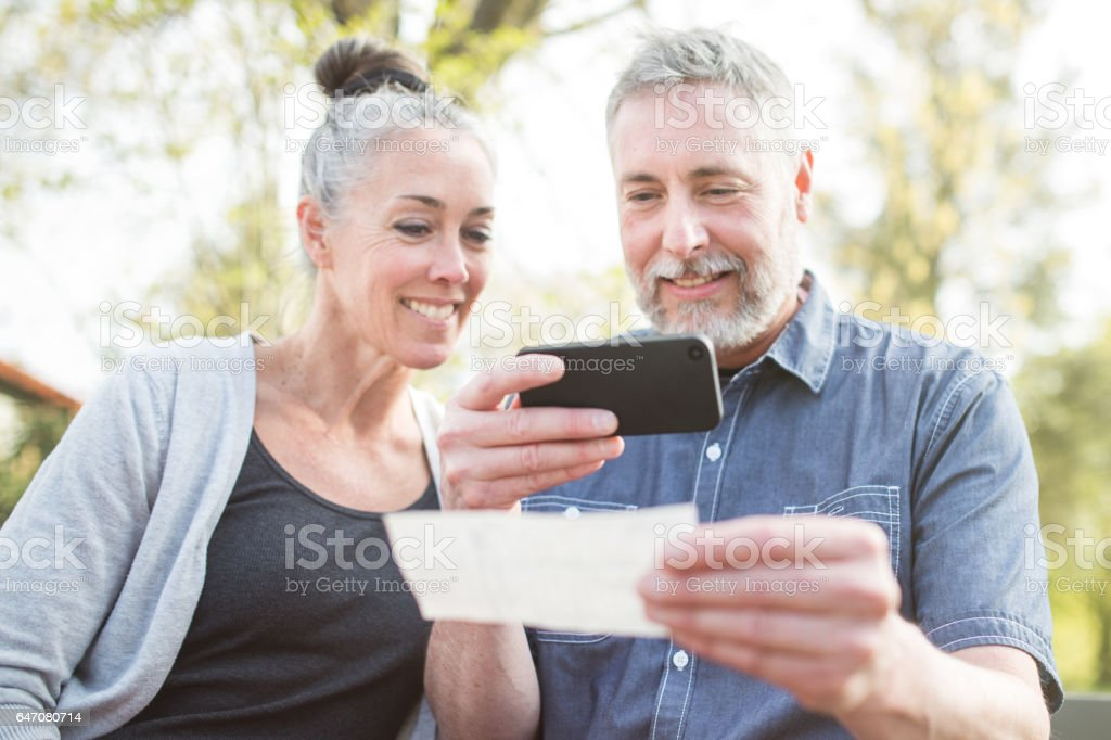 Mature Couple Remote Banking with Phone stock photo