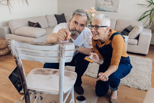 594910248 istock photo Mature couple repairing an old chair at home 1227153927