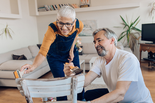 594910248 istock photo Mature couple repairing an old chair at home 1265724179