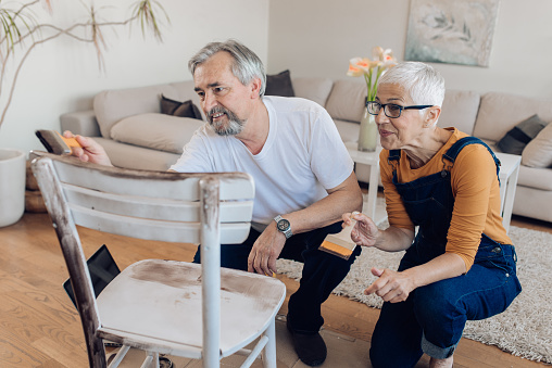 594910248 istock photo Mature couple restoring an old chair at home 1265724172