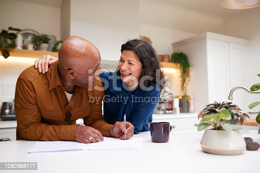 istock Mature Couple Reviewing And Signing Domestic Finances And Investment Paperwork In Kitchen At Home 1282868177