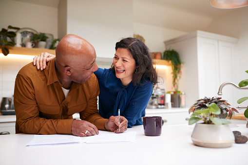 Mature Couple Reviewing And Signing Domestic Finances And Investment Paperwork In Kitchen At Home