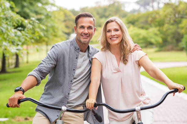 mature couple riding bicycle - mid adult couple stock pictures, royalty-free photos & images