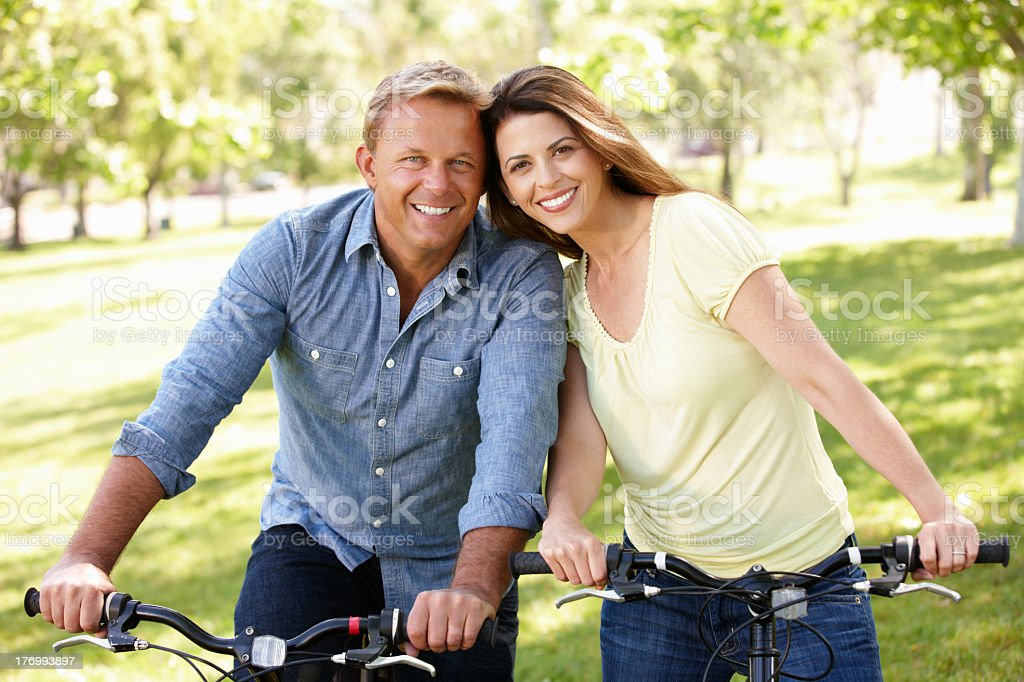 Mature couple riding bicycles in the park stock photo