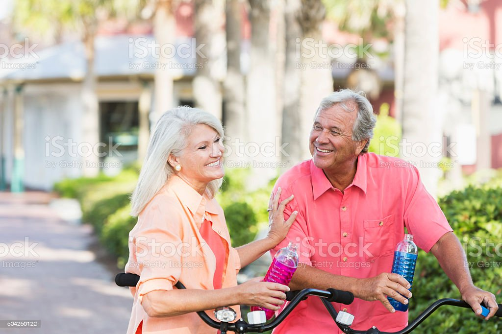 Mature couple riding bicycles on vacation stock photo