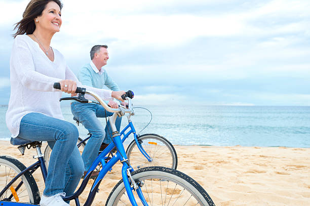 Mature couple riding bicycles stock photo