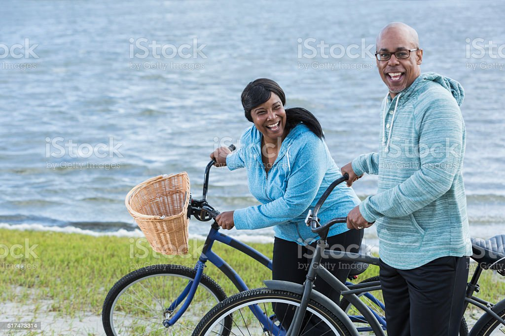 Mature couple riding bikes by water stock photo