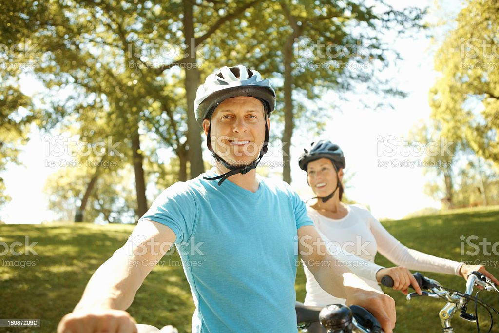 Mature couple riding bikes on a sunny day in the park royalty-free stock photo