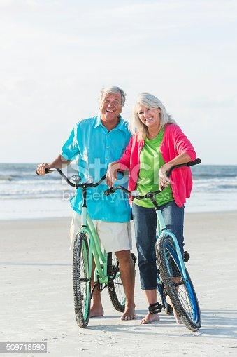 959016450 istock photo Mature couple riding bikes on the beach 509718590