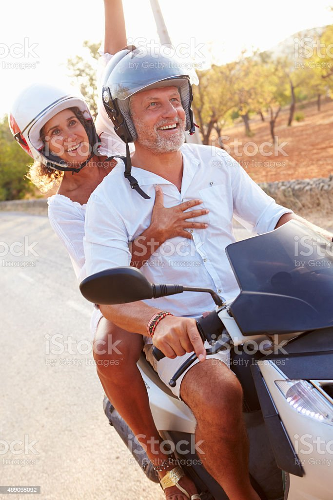 Mature Couple Riding Motor Scooter Along Country Road stock photo