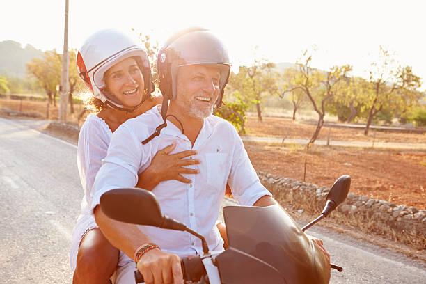 mature couple d'équitation de scooter sur route de campagne - moped photos et images de collection