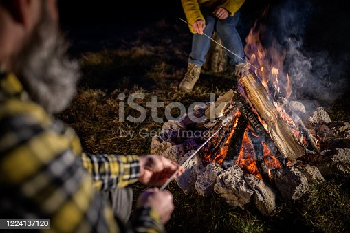 Elevated view of mature couple roasting marshmallow over campfire at dusk.