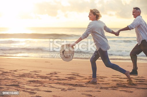Mature couple running and playing on the beach at sunset or sunrise. They are laughing and having fun. They are casually dressed. Could be a retirement vacation. They are back lit with lens flare