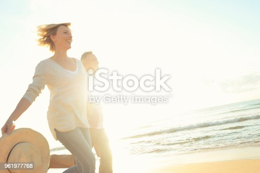 Mature couple running on the beach at sunset or sunrise. They are having fun, laughing and and smiling. The man has grey hair. Back lit with lens flare.