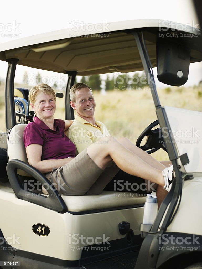 Mature couple seated in golf cart, smiling royalty-free stock photo