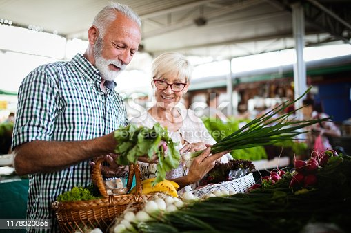 Senior couple shopping vegetables and fruits on the market. Healthy diet.
